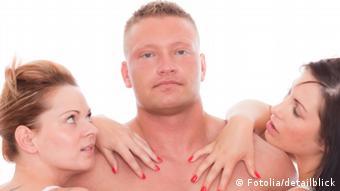 Symbolbild Weiberheld: Ein attraktiver Mann mit nacktem Oberkörper. Zwei Frauen stehen links und rechts von ihm und haben ihre Hände auf seinen Oberkörper gelegt.