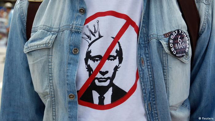 A participant wears a T-shirt with an image of Russian President Vladimir Putin during an opposition protest march in Moscow, June 12, 2013. Thousands of protesters marched in Moscow on Wednesday, calling for Putin's resignation and the release of activists facing long jail terms over violence at a rally on the eve of his inauguration to a third term last year. Badge reads Free prisoners of May 6. REUTERS/Maxim Shemetov (RUSSIA - Tags: POLITICS CIVIL UNREST)