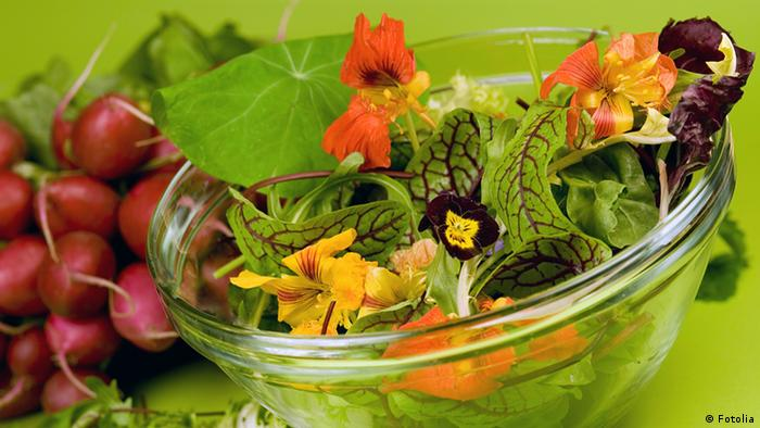 Eine Glasschale mit frischem Salat und Blumen, im Hintergrund Radieschen