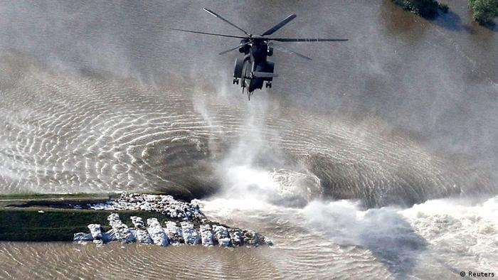 A helicopter of the German armed forces Bundeswehr drops sandbags next to a broken dam built to contain the swollen Elbe river during floods near the village of Fischbeck (photo: REUTERS/Tobias Schwarz)