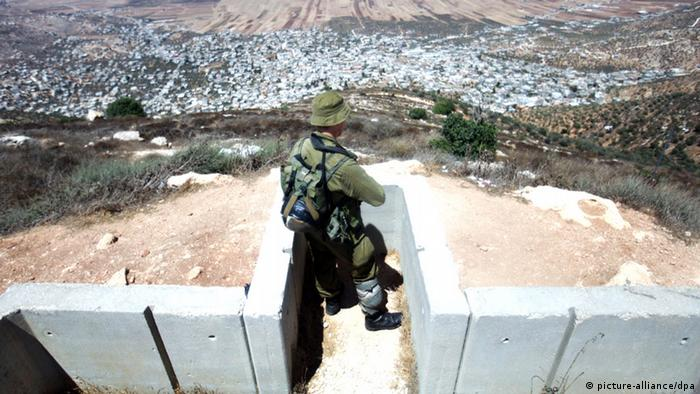 An Israeli soldier stands in a cement trench as he guards the Jewish settlement of Itamar in the West Bank (Photo: EPA/ABIR SULTAN)