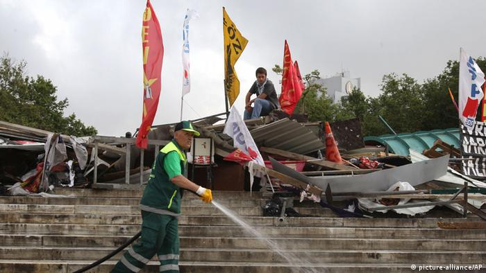 A municipality worker cleans with water the steps of Taksim Square as protester sits on a barricade in Istanbul on Thursday, June 13, 2013. Turkey's government on Wednesday offered a first concrete gesture aimed at ending nearly two weeks of street protests, proposing a referendum on a development project in Istanbul that triggered demonstrations that have become the biggest challenge to Prime Minister Recep Tayyip Erdogan's 10-year tenure. (AP Photo/Thanassis Stavrakis)