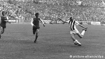 Günter Netzer (r) und zwei Spieler (links). Er ist dabei, den Ball zu schießen