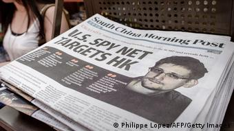 A woman walks past an edition of the South China Morning Post carrying the story of former US spy Edward Snowden on its front page in Hong Kong (photo: PHILIPPE LOPEZ/AFP/Getty Images)