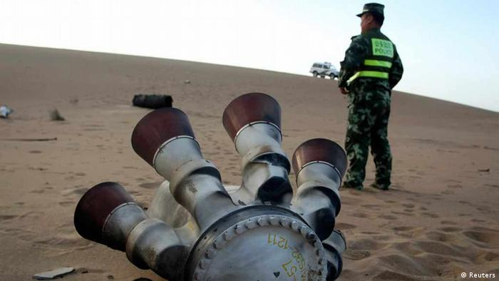 A policeman stands guard next to a component of the Shenzhou-10 manned spacecraft which was found in Badain Jaran Desert after the launch, 