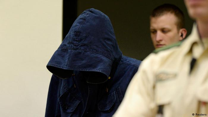 Co-defendant Carsten Schultze (L) hides his face under a hood as he arrives for another session of the trial at the regional courthouse in Munich, June 13, 2013. Schultze is on trial with Beate Zschaepe, 38, alleged member of the National Socialist Underground (NSU), charged with complicity in the murders of eight ethnic Turks, a Greek immigrant and a German policewoman between 2000 and 2007. REUTERS/Christof Stache/Pool (GERMANY - Tags: CRIME LAW)