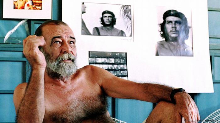 Ein Mann mit nacktem Oberkörper sitzt rauchend vor einer Wand, an die das Originalmotiv un der Ausschnitt mit dem berühmten Konterfei Che Guevaras gepinnt ist (Foto: Picture Alliance)