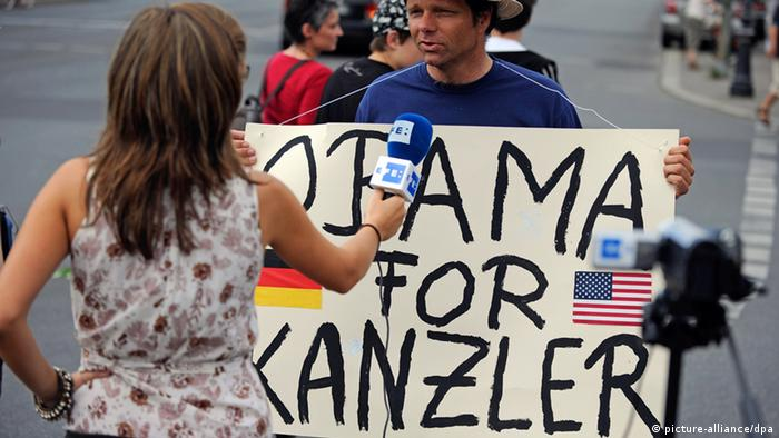 A man holds up a poster that says, 'Obama for chancellor.' Photo: Gero Breloer dpa/lbn +++(c) dpa - Bildfunk+++