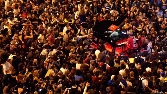 Davide Martello is surrounded by anti-government protesters as he performs at Taksim Square in central Istanbul