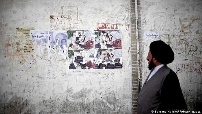 TO GO WITH AFP STORY BY FARHAD POULADI An Iranian clergyman walks past electoral posters of presidential candidates, former top nuclear negotiator, Hassan Rowhani (L) and former chief of the Revolutionary Guards, Mohsen Rezai, along a street in the religious Shiite city of Qom, some 130 kilometres south of the capital Tehran, on June 9, 2013. Iran's powerful bazaar merchants and Shiite clergy spearheaded the 1979 Islamic revolution, but their role on the country's political scene has waned with developments in society and the advent of new technology, analysts say. AFP PHOTO/BEHROUZ MEHRI (Photo credit should read BEHROUZ MEHRI/AFP/Getty Images)