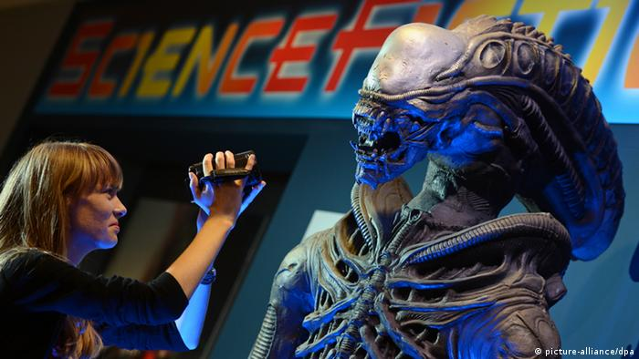 Woman filming statue of the alien from the Alien movies at an exhibition. (Photo: Hendrik Schmidt/dpa)