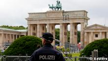 A police officer stands guard in front of the Brandenburg Gate where U.S. President Barack Obama will give a speech during his visit in Berlin, June 14, 2013. U.S. President Barack Obama will visit Berlin on June 18th to 19 and the visit comes nearly 50 years to the day after John F. Kennedy landed in a divided Berlin at the height of the Cold War and told encircled westerners in the city Ich bin ein Berliner, a powerful signal that America would stand by them. REUTERS/Fabrizio Bensch (GERMANY - Tags: CRIME LAW POLITICS)