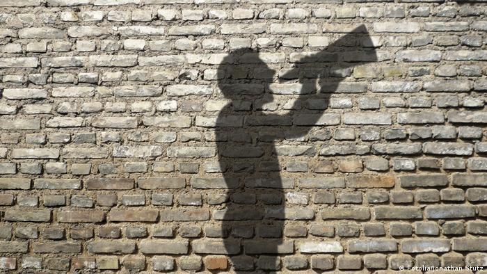 Auf einer Mauer ist der Schatten eines Mannes zu sehen, der in ein Megaphon spricht