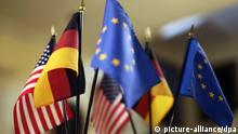 Ein Fahnenständer mit einer USA-, Deutschland- und Europaflagge steht vor einem Spiegel im Loeb-Haus an der Havard Universität in Boston, aufgenommen am 12.04.2008. Foto: Arno Burgi dpa +++(c) dpa - Report+++