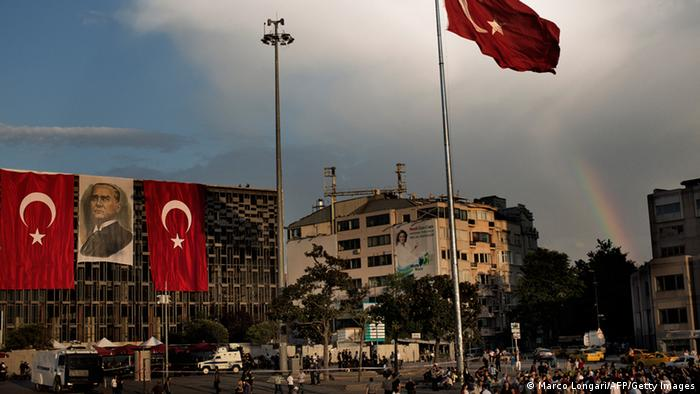A rainbow is seen as giant national flags and a portrait of Mustafa Kemal Ataturk are displayed on Istanbul Taksim square June 14, 2013. AFP PHOTO / MARCO LONGARI (Photo credit should read MARCO LONGARI/AFP/Getty Images)