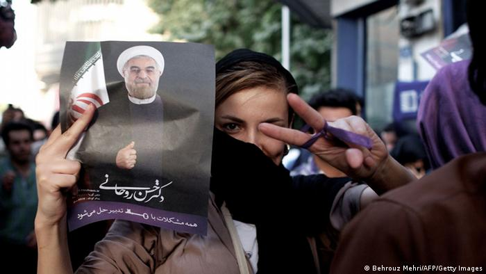 An Iranian woman flashes the sign for victory as she holds a portrait of moderate presidential candidate Hassan Rowhani during celebrations after he won the Islamic Republic's presidential elections in downtown Tehran on June 15, 2013. Iranian Interior Minister Mohammad Mostafa Najjar said Rowhani won outright with 18.6 million votes, or 50.68 percent. AFP PHOTO/BEHROUZ MEHRI (Photo credit should read BEHROUZ MEHRI/AFP/Getty Images)