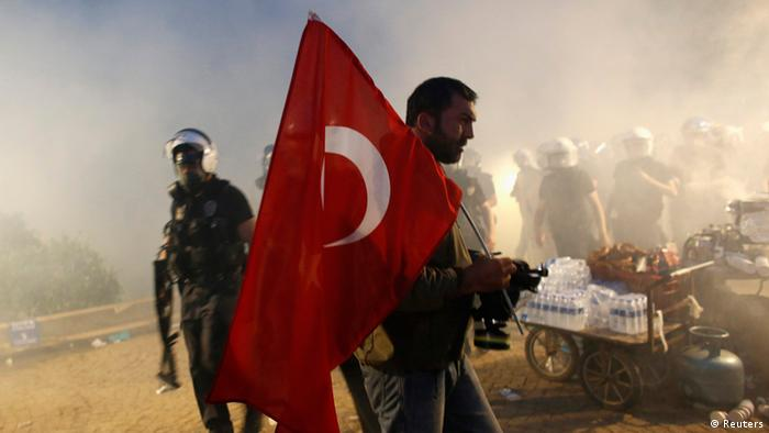 A protester holds a Turkish flag as riot police order them to evacuate Gezi Park in central Istanbul June 15, 2013. Thousands of people took to the streets of Istanbul overnight on Sunday, erecting barricades and starting bonfires, after riot police firing teargas and water cannon stormed a park at the centre of two weeks of anti-government unrest. Lines of police backed by armoured vehicles sealed off Taksim Square in the centre of the city as officers raided the adjoining Gezi Park late on Saturday, where protesters had been camped in a ramshackle settlement of tents. Picture taken June 15, 2013. REUTERS/Murad Sezer (TURKEY - Tags: POLITICS CIVIL UNREST CRIME LAW)