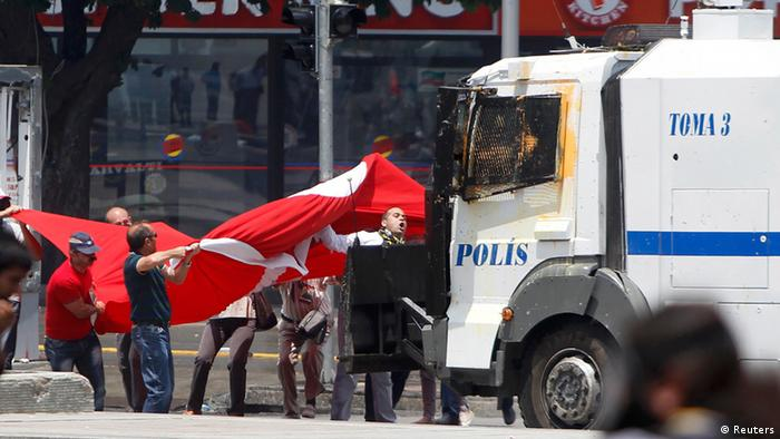 Protesters confront a Turkish riot police water cannon vehicle during a demonstration at Kizilay square in central Ankara June 16, 2013. Thousands of people took to the streets of Istanbul overnight on Sunday, erecting barricades and starting bonfires, after riot police firing teargas and water cannon stormed a park at the centre of two weeks of anti-government unrest. Lines of police backed by armoured vehicles sealed off Taksim Square in the centre of the city as officers raided the adjoining Gezi Park late on Saturday, where protesters had been camped in a ramshackle settlement of tents. REUTERS/Dado Ruvic (TURKEY - Tags: CIVIL UNREST POLITICS)