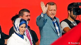 Turkish Prime Minister Tayyip Erdogan waves hand as he arives with his wife Emine at a rally of ruling AK party in Istanbul June 16, 2013. (TURKEY - Tags: POLITICS CIVIL UNREST)
