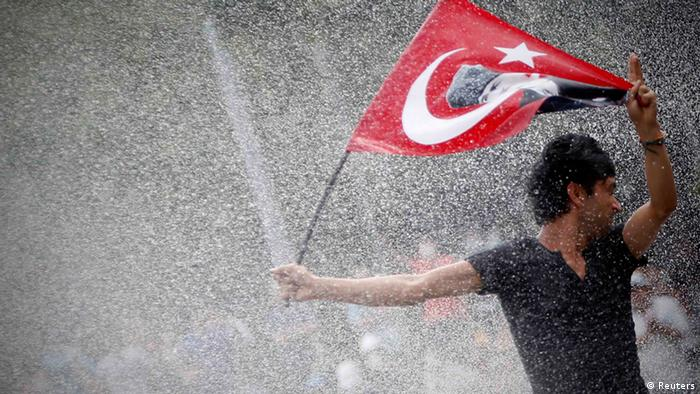 A young man waving a Turkish flag and turning his face away under a heavy spray of water (REUTERS/Serkan Senturk)