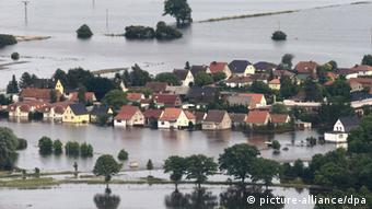 A community of houses stands flooded in water 
