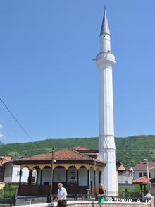 The white minaret of the Suzi mosque raises into the blue sky.
