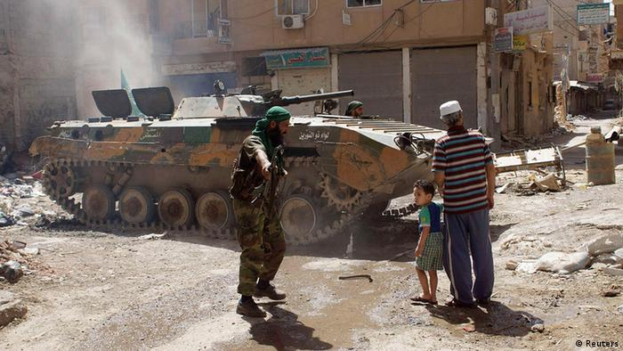 A member of the Free Syrian Army gestures to a child in Deir al-Zor, June 16, 2013. Picture taken June 16, 2013. REUTERS/Khalil Ashawi (SYRIA - Tags: CONFLICT)