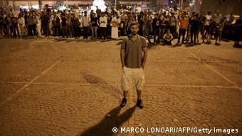 A man emulates Turkish choreographer Erdem Gunduz by standing on Taksim square for a lone protest June 18, 2013. Gunduz had stood for several hours unnoticed before his presence on the flashpoint square went viral on the social network Twitter. He was then joined by hundreds of others who in solidarity decided to join his protest by standing for hours on end. Turkish police intervened clearing the square and arresting several demonstrators. AFP PHOTO/MARCO LONGARI (Photo credit should read MARCO LONGARI/AFP/Getty Images)