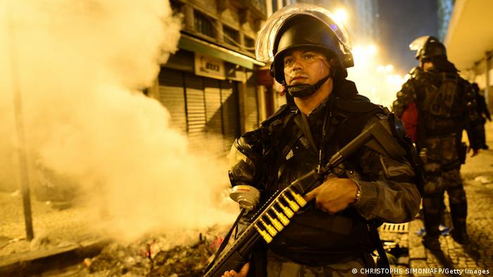 A riot police officer holds a weapon during clashes in Rio de Janeiro s AFP PHOTO / CHRISTOPHE SIMON (Photo credit should read CHRISTOPHE SIMON/AFP/Getty Images)