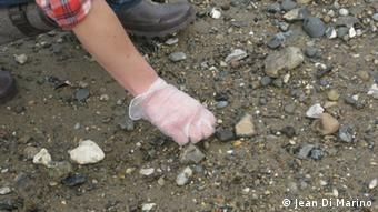 A close up of a woman's hands in latex gloves poking around in the mud(Photos:Jean Di Marino for DW)