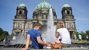 Пара сидит у фонтана в Берлине