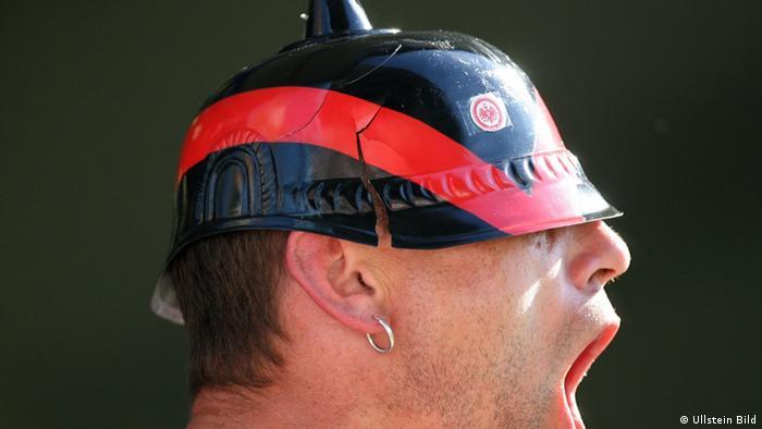 Fan von Eintracht Frankfurt bruellt und traegt einen Fussball-Helm im Stil der historischen Pickelhaube (Copyright: Ullstein)