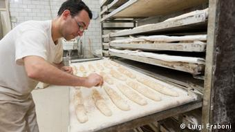 At Il Fornaio bakery, Michele D'Aloisi carefully sprinkes sesame seeds on every loaf. Artisan bakeries are closing in Sicily, victims of the crisis, Mafia extortion and the trend to buy industrial bread from supermarkets. (photo by Luigi Fraboni)