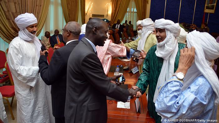 Members of the Malian and the Tuareg delegations shake their hands after signing an agreement at a meeting on the Malian crisis on June 18, 2013 in Ouagadougou. The Malian government and Tuareg rebels occupying a key northern city signed an accord today paving the way for presidential elections in the west African state next month. Mali's territorial administration minister and representatives of two Tuareg movements signed the deal in Ouagadougou, capital of neighbouring Burkina Faso, as the lead mediator in negotiations, Burkinabe President Blaise Compaore, looked on. AFP PHOTO AHMED OUOBA (Photo credit should read AHMED OUOBA/AFP/Getty Images)