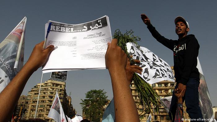 epa03705081 Egyptian protesters hold applications for 'Tamarod', for a campaign calling for the ouster of Egyptian President Mohammed Morsi and for early presidential elections, during a protest in Tahrir Square, in Cairo, Egypt, 17 May 2013. Hundreds of demonstrators called for the removal of President Morsi, the Muslim Brotherhood and early elections. EPA/KHALED ELFIQI