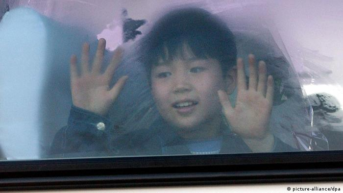 A young North Korean defector waves through a bus window, 18 March 2002, on its way to the South Korean capital after landing at Incheon international airport from Manila. (Photo: dpa)