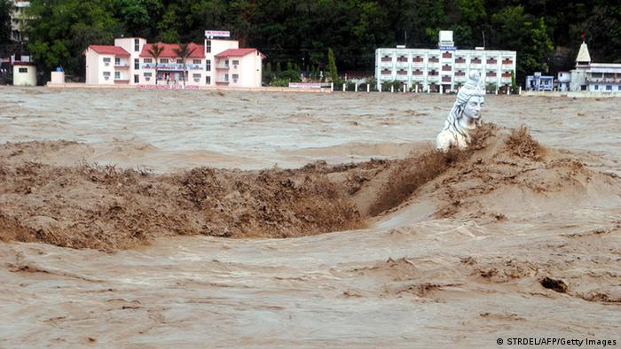Fast moving water flows over a Hindu statue during a heavy monsoon rain in Rishikesh town in the Indian state of Uttrakhand on June 17, 2013. Heavy rains lashed parts of north India Monday, resulting in the deaths of at least 18 people, as the annual monsoon covered the country nearly two weeks ahead of schedule, officials said. More than a dozen people lost their lives due to record downpours in Uttarakhand state, situated in the foothills of the Himalayas, a local official said. AFP PHOTO/ STR (Photo credit should read STRDEL/AFP/Getty Images)