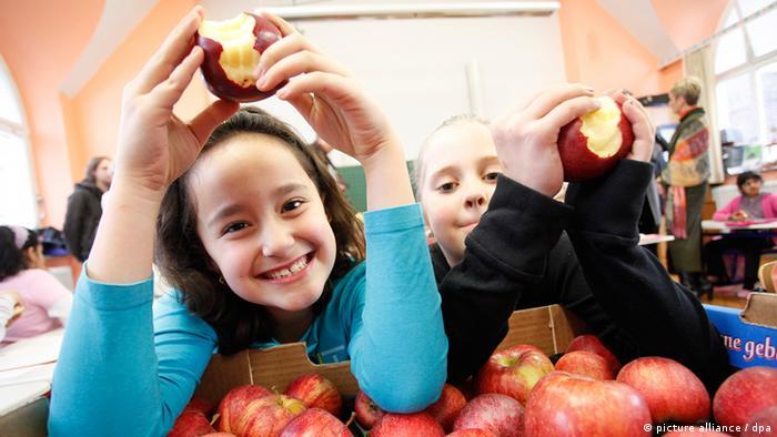 Schülerinnen essen Äpfel