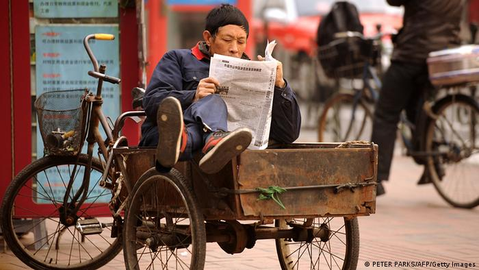 A man reads a newspaper while sitting in his tricycle on a street in Shanghai