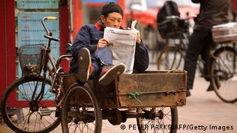 A man reads a newspaper whilst sitting in his tricycle on a street in Shanghai on January 9, 2013 (Peter Parks)
