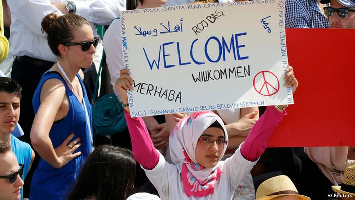 A Turkish-German girl holds up a welcoming placard as she watches U.S. President Barack Obama
