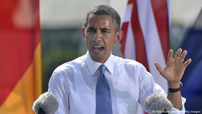 US President Barack Obama (R) delivers a speech at the Brandenburg Gate