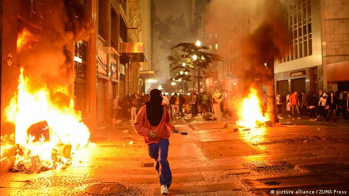 June 18, 2013 - Sao Paulo - A man runs through the burning streets as demonstrators take part in a protest organized by the Pase Libre Movement. Brazil's government says it will deploy a national security force to five major cities after a wave of protests which has seen almost a quarter of a million people demand better public services. The national force will be sent to Rio de Janeiro, Belo Horizonte, Salvador, Fortaleza and the capital, Brasilia. All of the cities are hosting games in Fifa's Confederations Cup