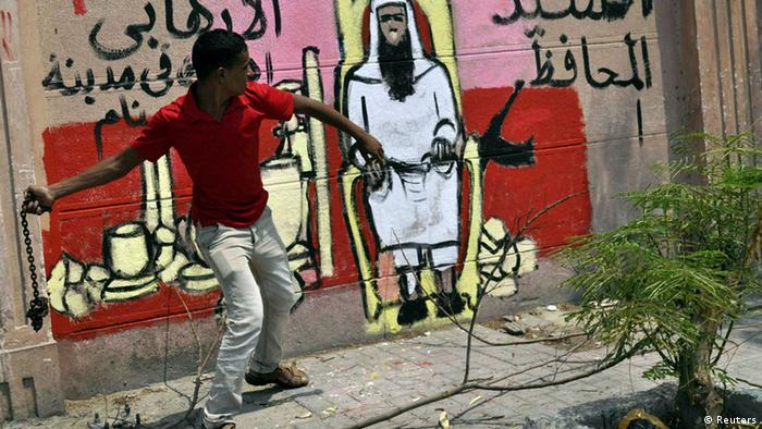 A protester throws a chain next to a graffiti on the wall depicting the newly appointed governor of Luxor Adel Mohamed al-Khayat, as a terrorist, as protests gather in front of the goverorate building to protest his appointment in Luxor, June 19, 2013. Al-Khayat was a member of the militant group blamed for slaughtering 58 tourists in Egypt's Valley of the Queens; today he's promising to keep visitors safe. Khayat's appointment by President Mohamed Mursi as governor of the city of Luxor has triggered howls of protest, with demonstrators protesting for a third day on Wednesday and one critic calling it the last nail in the coffin of tourism. REUTERS/Stringer (EGYPT - Tags: POLITICS CIVIL UNREST)