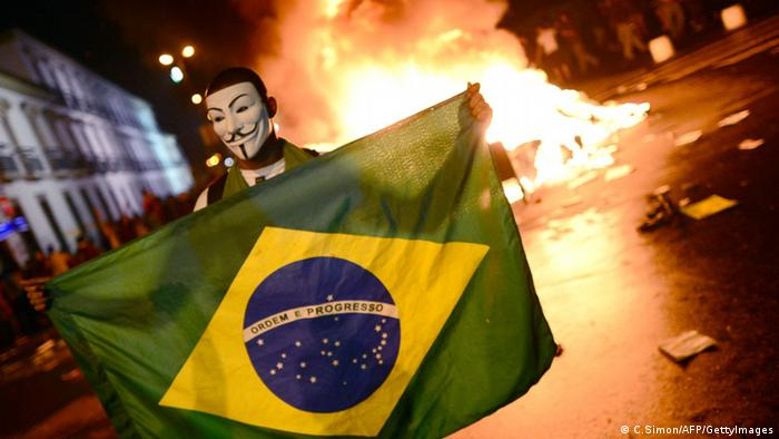 A demonstrator wearing a Guy Fawkes mask holds a Brazilian national flag during clashes in downtown Rio de Janeiro on June 17, 2013, after a protest against higher public transportation fares and the use of public funds to finance international football tournaments. Protesters in several major cities are up in arms over hikes in mass transit prices -- from $1.5 to $1.6 -- as well as over the $15 billion earmarked for the two sports events amid calls for more health and education funding. AFP PHOTO / CHRISTOPHE SIMON (Photo credit should read CHRISTOPHE SIMON/AFP/Getty Images)