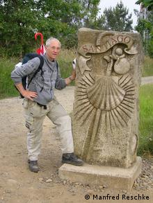 Manfred Reschke poses with a statue during a hike in Santiago