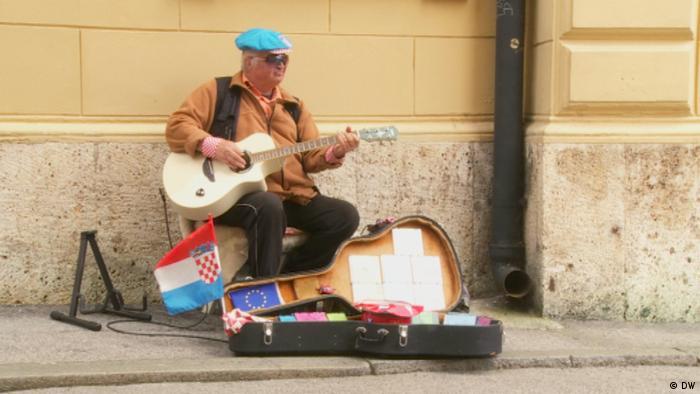 Musiker auf dem Markusplatz in Zagreb, Kroatien. Kroatische Mini-Flagge weht an seinem Gitarrenkoffer, daneben eine Karte mit den 12 Sternen der Europaflagge; Copyright: DW