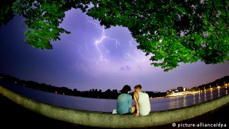 A couple sits on the waterfront and a lightning is seen in the sky