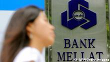 A woman walks past a signboard of Bank Mellat, an Iranian state-run commercial bank, outside its Seoul branch in Seoul on September 8, 2010. South Korea said it would penalise a key Iranian bank and put all financial transactions with Tehran under strict government supervision as part of sanctions over its nuclear programme. AFP PHOTO/PARK JI-HWAN (Photo credit should read PARK JI-HWAN/AFP/Getty Images)