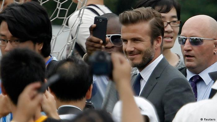 Former England captain David Beckham (obscured) arrives at Tongji University surrounded by his fans in Shanghai June 20, 2013. Beckham cancelled his event at Tongji University after a stampede accident happened upon his arrival injuring at least five people on Thursday, local media reported. REUTERS/Aly Song (CHINA - Tags: SPORT SOCCER)